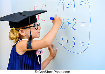 arithmetic - Cute little student girl in academic hat during...