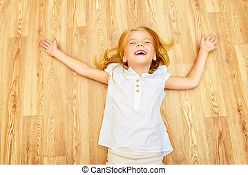 happy delight - Cute joyful girl lying on a floor at home.