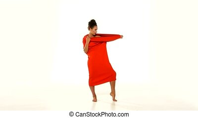 Brunette young woman wearing on the head unusual long red dress-changeling white background