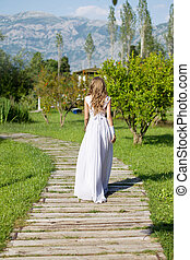Bride walking along the path to the altar view from back