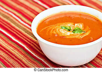 Tomato soup garnished with cream and basil leaves