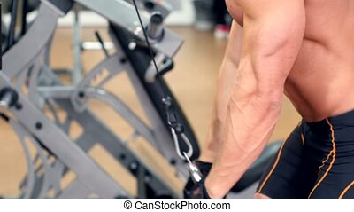 Side view of muscular sportsman doing weight lifting press lower unit to top in the gym, cam moves upwards