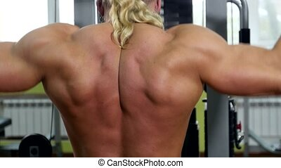 Back view of bodybuilder doing exercises on the trainer,...