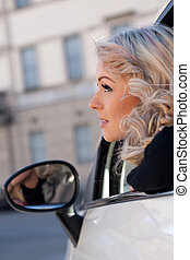 tourist watches something from her car - blonde tourist...
