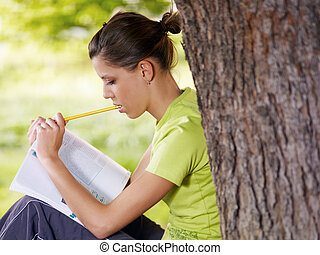 college student - young woman studying outdoors and leaning...