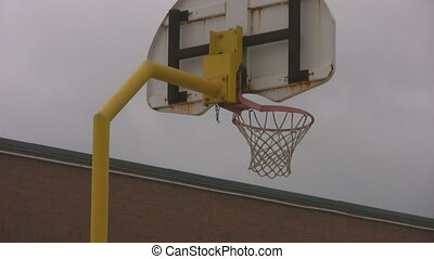 Outdoor basketball net closeup and school yard zoom out