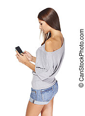 Teen girl text messaging on her mobile - Side view of teen...