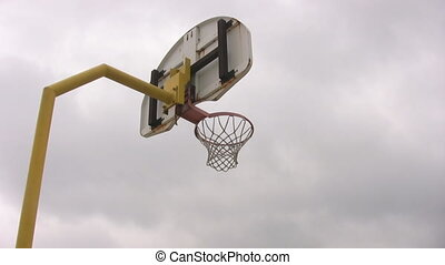 Looking up at outdoor basketball net and panning - Looking...