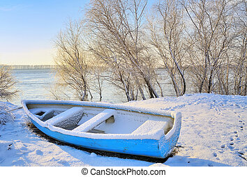 blue boat near danube river in winter time