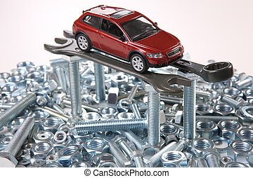 repair of car - red toy car on wrenches bolts and nuts