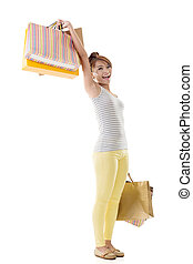 Cheerful shopping woman of Asian holding bags, isolated