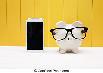 Piggy bank wearing glasses with cellphone - Piggy bank...