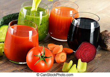 Glasses with fresh organic vegetable juices on wooden table....
