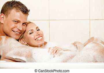 Royal bath - Smiling young couple enjoying bubble bath