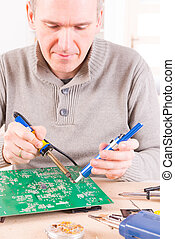 Serviceman soldering on PCB - Serviceman soldering PCB with...