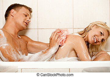 Man bathing his wife - Young guy scrubbing his wifes back