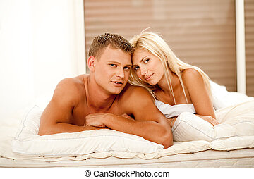 Mid adult couple lying in bed