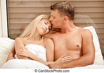 Mid adult man kissing girlfriends\'s forehead - Young man...