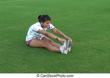 Stretching - Young Latin American woman stretches to warm up...