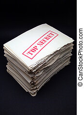 stack of secret documents on black background