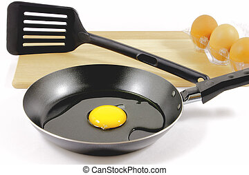 Teflon pan and eggs - Three shell eggs, uncooked egg in a...
