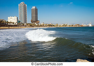 Waves at a beach in Barcelona with two skyscrapers in the...