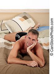 Man bedroom grooming - Handsome forties man grooming on bed...