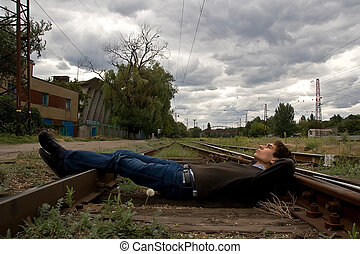 Young man laying on a railway tracks