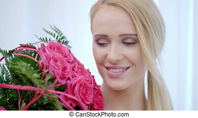Happy Pretty Woman with a Bouquet of Pink Roses