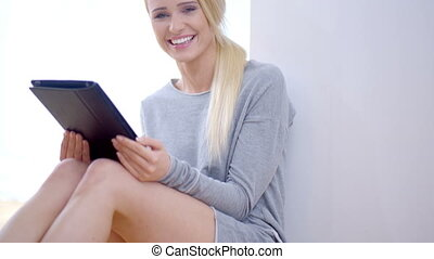 Happy young woman using a tablet computer