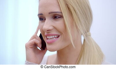 Pretty blond woman talking on her mobile