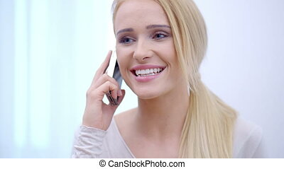Pretty blond woman listening to a mobile call - Pretty blond...