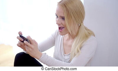 Excited young woman reading an sms on her mobile exclaiming...