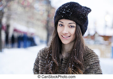 Young beautiful woman in stylish mink coat on a background...
