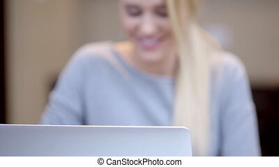 Smiling young woman working on a laptop