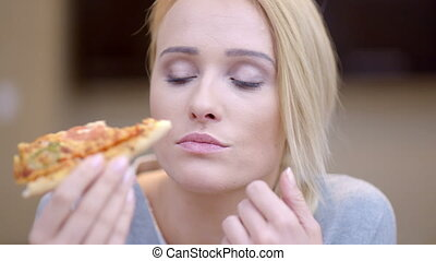 Attractive woman eating homemade pizza - Attractive woman...