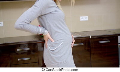 Pregnant young woman standing in her kitchen gently...