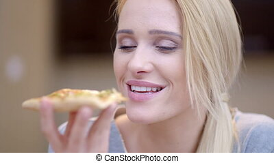 Attractive woman enjoying a slice of pizza biting into it...
