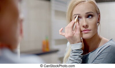 Pretty Blond Woman Applying Eyebrow Makeup - Close up Pretty...