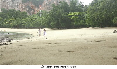 bride and groom run along beach under rain