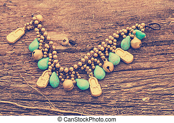 turquoise stone and golden necklace on wooden background.