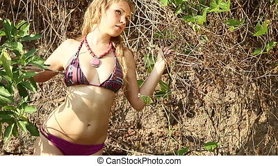 pretty blonde girl in swimsuit and necklace poses for camera...