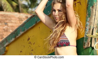 blonde girl in swimsuit and necklace poses for camera -...