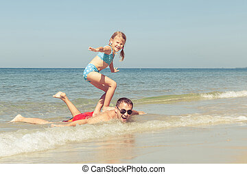 Father and daughter playing on the beach at the day time...