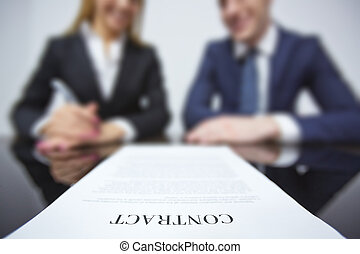 Business contract on workplace with two colleagues on...