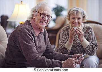 Happy older man - Senior man with touchpad looking at camera...
