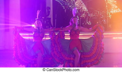 two girls in cabaret costumes dance cancan