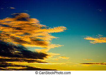 Golden clouds on dark blue sky in late evening
