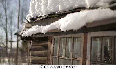 Spring thaw - Spring snow melting on the roof old house