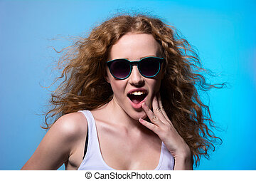 Pretty young emotional girl in sunglasses on a blue...